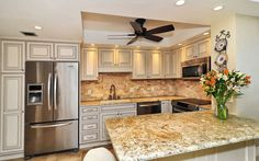 Beautiful Mixed Marble 2x4 Mosaic Backsplash using Crossville Modern Mythology Muse. Focal created by using coordinating mini mosaics with pencil liner frame. Countertop is Colonial Gold Granite. White cabinetry adds sophistication to this classic look.    Photo Credit: Pix360.com