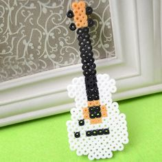 Perler Bead Guitar This cool guitar is easy to make using Perler Beads. Its a fun project to accompany a study of music. The post Perler Bead Guitar was featured on Fun Family Crafts. Perler Bead Designs, Diy Perler Bead Crafts, Easy Perler Bead Patterns, Melty Bead Patterns, Perler Bead Templates, Hama Beads Design, Diy Perler Beads, Perler Bead Art, Beading Patterns