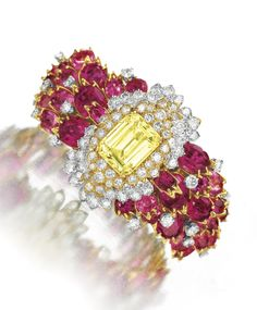 A DIAMOND, RUBELLITE TOURMALINE AND YELLOW SAPPHIRE BRACELET, BY DAVID WEBB Set with a rectangular-cut yellow sapphire, within a circular-cut diamond foliate surround, to the variously-shaped rubellite tourmaline cluster band with circular-cut diamond detail, mounted in gold and platinum, circa 1966, 6 ins., in a David Webb black leather case