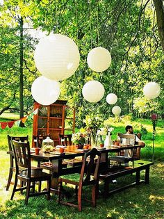 indoor furniture outdoors - farmhouse wood table party - white lanterns - flag bunting