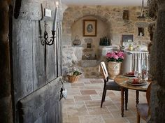 i'm melting over this charmed room..complete with antique wood door and stone walls