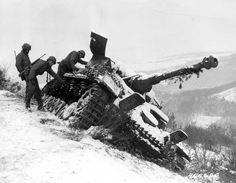 American soldiers inspect a destroyed German Panzer IV on the side of the road near Goesdorf, Luxembourg.