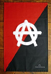 """Anarchist tea towel  The famous A and O symbol, daubed onto a hastily painted red and black background. Let's face it, if you're an anarchist you don't stand on ceremony. The letters stand, apparently, for """"Anarchism"""" and """"Order"""". The symbol first gained currency in Spain in the late 19th century. It became particularly well known when it was taken up by the anarcho punk movement in the 1970s."""
