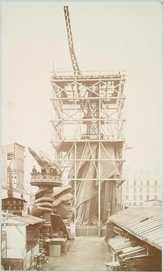 Assemblage of the Statue of Liberty in Paris, showing the bottom half of the statue erect under scaffolding, the head and torch at its feet.