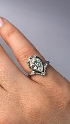 Such a beautiful and unique ring! This vintage gemmy beauty is so elegant on the finger, with the sparkly central transitional cut diamond framed beautifully by a halo of emeralds. This ring is representative of why we love the Art Deco era so much, the old cut stones are perfectly complemented by the delicate yet finely crafted platinum setting. The 1.20ct transitional stone is bezel and bead set, surrounded by a halo of channel set calibre cut emeralds. There is also an additional 0.17ctw…