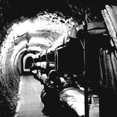 WORLD WAR II: BOMB SHELTER. A woman kneeling beside a girl in a bunk bed in a bomb shelter located in a subway tunnel beneath London England during World War II. Photographed by Tony Frissell. World History, World War Ii, Bomb Shelter, The Blitz, Air Raid, Battle Of Britain, London Underground, Underground Shelter, Underground Tube