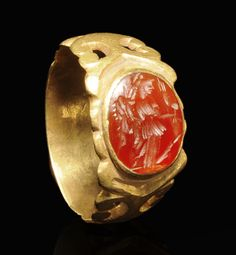ROMAN GOLD RING WITH CARNELIAN INTAGLIO OF FORTUNA (TYCHE)  The goddess of good luck and destiny holding a cornucopia and rudder. Wide band with ornamental openwork.  2nd-3rd Century AD