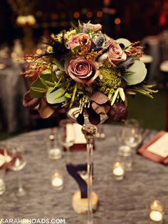 This is a vintage centerpiece done right. These dark mauve of these roses with the lime green and slivery tones of the greenery and the pops of black are a perfect combination.