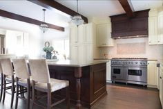 This kitchen features a stainless steel oven, stove and a wood range hood that connects to the ceiling's exposed beams. The miniature chandeliers give a classic touch to this traditional kitchen.