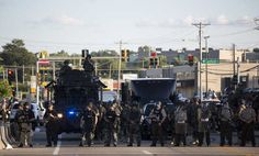Police officers keep watch while demonstrators (not pictured) protest the death of black teenager Michael Brown in Ferguson, Missouri August 12, 2014. Police said Brown, 18, was shot in a struggle with a gun in a police car but have not said why Brown was