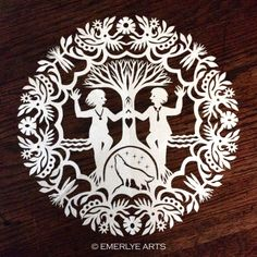 A custom kirigami mandala by Cynthia Emerlye for a woman who loves dancing, wolves, ancestry tree, and garden.