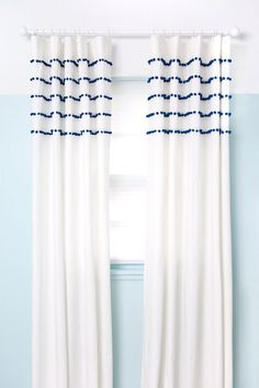 Make a whimsical pair of pom pom striped curtains for surprisingly little money.