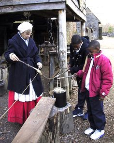 YORKTOWN VICTORY CENTER: An interpreter helps two young visitors take part in candle-dipping activities at the farm.