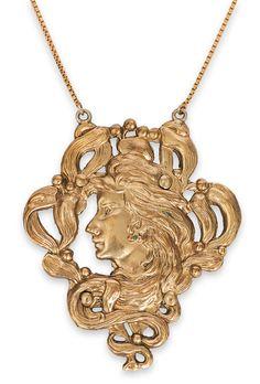 An Art nouveau pendant    C. 1910. 8 ct. yellow gol. Stylized female head. Chain 18 kt. yellow gold (add.). Pendant: 65 x 5 mm, chain length 38 cm, weight ca. 14 g.