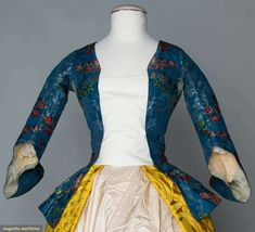 Augusta Auctions  BLUE SILK BROCADE BODICE, 1750-1770       French blue faille ground, patterns of ivory lace & garden flowers in red & plum shades, V at CF & CB, attached peplum w/ pleats at back sides, fitted elbow L sleeves w/ deep cuffs, homespun linen bodice lining, ice blue silk facing & peplum