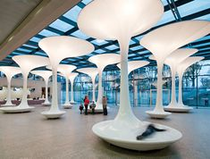 multifunctional furniture made of glass-fibre reinforced plastic, fabric and enveloped the steel columns. 'trees' provide seating, shade and acoustic absorption and at night they serve as an illuminate bodies which fill the room with white or blue glowing light