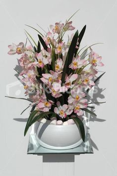 Pink orchid display, amazing quality, real touch and ultra realistic. Comes fully assembled in a round white vase, ready to sit in place. Beautiful modern pink orchid vase display ideal for your home. A mixture of fresh touch cymbidium orchids and orchid leaves.Vase display ideal for reception desks in spas, hotels and restaurants. Finished off with pink and white marshmallows. Flowers can be changed to any desired colour or species. Vase display measures approximately 60cm tall.