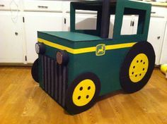 John deere tractor made from a box. I cut, glued, crafted and painted this for my nephews bday party. Its made out of heavy duty cardboard.