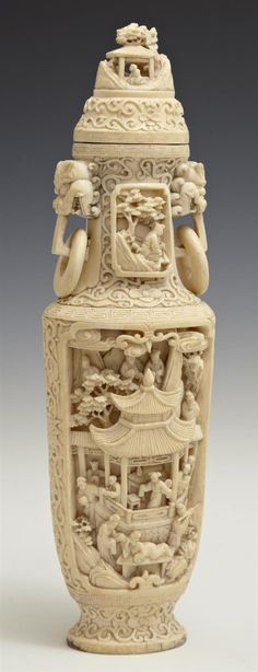 Chinese Carved Ivory Lidded Vase, mid 20th c., of tapered oval form, with Foo lion ring handles, two sides with high relief landscape and figural panels within overall relief scrolled foliate decoration, on a carved hardwood stand, H.- 10 1/4 in., W.- 2 7/8 in., D.- 2 1/2 in.