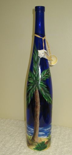 This is for a large 19 colbalt blue wine handpainted wine bottle. Beach Scene includes plams, beach, ocean, other tropical plants. Also Wine bottle includes a pair of dangling seashells. Recycled Wine Bottles, Painted Wine Bottles, Lighted Wine Bottles, Decorated Bottles, Glass Bottles, Glass Bottle Crafts, Wine Bottle Art, Beer Bottle, Wine Craft
