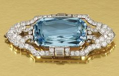 AQUAMARINE AND DIAMOND BROOCH/PENDANT, 1920S Centring on a cut-cornered step-cut aquamarine within a geometric frame embellished with circular-, single-cut and cushion-shaped diamonds.
