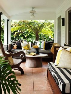 This covered sunporch makes the most of its tropical surroundings. The daybeds, outfitted with bold striped seat cushions, offer plenty of seating. Sunshine yellow accents scattered throughout the space help break up the strong black-and-white palette. #porchlayouts #patiodecor #porchideas #outdoorfurniture #bhg Outdoor Rooms, Outdoor Gardens, Outdoor Living, Outdoor Decor, Outdoor Kitchens, Outdoor Patios, Outdoor Seating, Outdoor Lounge, Indoor Outdoor