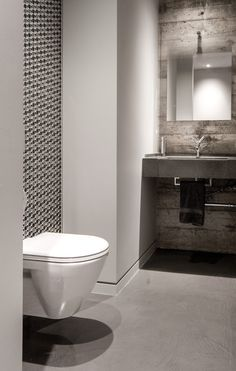 Falken Reynolds - Modern powder room in our bachelor pad loft features a wall of glass steel & porcelain mosaic tile, Axor Strack faucet, concrete counter, glas Italia mirror, exposed formed concrete walls, led accent cove lighting and a wall hung toilet