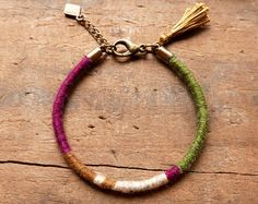Delicate and soft boho bracelet, winter colors, for ladies. This bracelet is hand-woven with different fines and luxurious wools, Merinos wool, cashmere and wool/cotton. It is ended with a silk tassel that enhances with its brightness, the matte and warmth side of the wool and add to the bracelet a delicate and feminine touch.  Thanks to an amature in copper wire which is integrated into the weaving and completely invisible, the shape of the bracelet is easily adjustable and re-adjustabl...