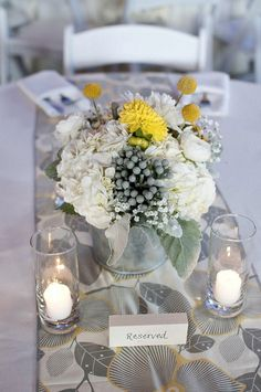 white, grey and yellow centerpieces with patterned table runner. love this patterned table runner! would look so pretty on a white table cloth.