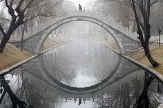 shaped half circle bridge reflects over the river / ponte em forma de semi-círculo reflete sobre o rio