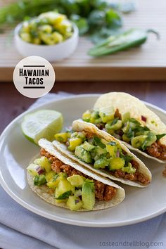 Hawaiian Tacos - 1 lb ground pork; 1/2 c prepared bbq sauce; 1/4 c diced red onion;   1 jalapeno, ribs  seeds removed, minced; 1/2 c chopped cilantro; Juice from 1 lime; 1 c diced fresh pineapple; 1 avocado, diced;   1 mango, diced; 1 pkg (4.6 oz) Old El Paso® taco shells (8 shells), warmed according to package directions