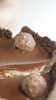 Recipe with video instructions: Ferrero Rocher Cheesecake recipe Ingredients: 8 ½ oz of crushed corn flakes, 2 ½ oz  unsalted butter, melted, 4 tbsps cocoa powder, 7 oz hazelnut, 1.1 lbs cream cheese, 1 ½ cup + 4 tbsps cream (25% fat content), 3 oz sugar, ½ teaspoon vanilla extract, 170g dark chocolate, 8 Ferrero Rocher chocolates