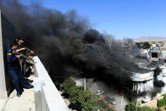 アフガニスタン・へラート(Herat)州ヘラート市にあるインド領事館への武装集団の攻撃を受け、周辺の建物の屋上で警戒する警察官たち(2014年5月23日撮影、資料写真)。(c)AFP=時事/AFPBB News