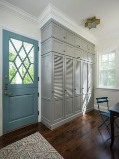 A turquoise blue door opens to a mudroom features built-in gray louvered locker cabinets adorned with dark brass knobs illuminated by a brass star shaped flush mount light, Sophia Flush Mount. Mudroom Cabinets, Mudroom Laundry Room, Grey Cabinets, Closet Mudroom, Garage Closet, Grey Front Doors, Front Door Colors, Blue Doors, Solid Doors
