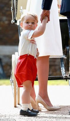 George was dressed in an outfit of red shorts and a white embroidered shirt...