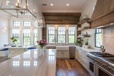 A pair of glass and nickel lanterns hang over a kitchen island topped with gray stripe marble lined atop an oak floor. An oak French kitchen hood, flanked by windows, stands over a gray striped marble backsplash and a stainless steel stove and pot filler with stacked oak shelves to the left. A farmhouse sink stands flanked by a stainless steel dishwasher to the right and a stainless steel mini fridge to the right is placed under a stained oak backsplash.