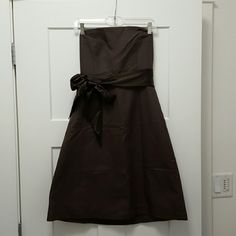 J Crew Brown Cotton Strapless Dress J Crew Brown Cotton Strapless Dress.  Lined, comes with removable brown satin sash. Size 6. No flaws, just needs to be ironed.  The crease on the bodice in the first picture is just because it needs to be ironed, it's not a design feature. It zips up the back. J. Crew Dresses Strapless