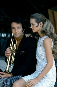 Cheryl Tiegs sitting with trumpet player Herb Alpert, 1967