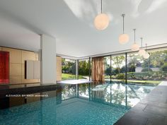 The pool with a floor made of iridescent glass mosaic is made from natural stone - from Tauern- gruen, as used for the floor. Haus su in Stuttgart, Germany by Alexander Brenner Architekten