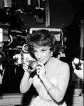 Medium BTS shot of Gina Lollobrigida as Carla Vesari holding camera.