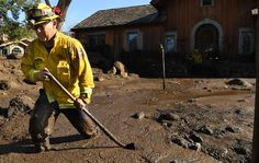 Cal Firefighter Alex Jimenez walks out after marking a spot with a stick where he found a body under the mud at a house along Glen Oaks Drive (Getty)