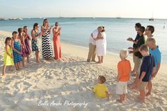 Renewal of vows on Marriott's beach surrounded by family as they embrace and seal it with a kiss