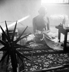In 1946, Mohandas Gandhi sits next to a spinning wheel, a device used to make yarn or thread