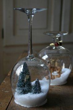 """Uit karton een """"deksel"""" tekenen en uitknippen, hierop de boompjes/rendieren plakken (met lijmpistool), wijnglas vullen met een beetje sneeuw, daarna """"deksel"""" vastplakken op de bovenkant met lijmpistool, daarna omdraaien.. Evt randje bedekken met lijm en extra sneeuw"""