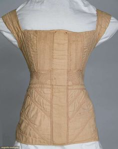 """Corded cotton corset, 1825-1830. Augusta Auctions: """"Tan hand woven cotton, cording in vertical rows, diagonal rows & arches, hand stitched in red & pink, CF casing for busk, 9 pair ivory eyelets for back lacing, B 30"""", W 24"""", CFL 15.5"""" Brooklyn Museum"""""""