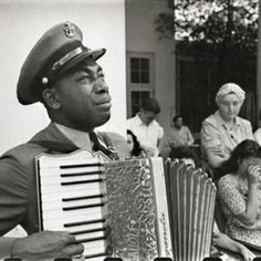 "This photo captures an openly weeping Chief Petty Officer (USN) Graham W. Jackson playing ""Goin' Home"" on his accordion while FDR's flag-draped casket leaves Warm Springs, Arkansas on April 13,  1945. This photo, taken by Ed Clark, has come to not only symbolize the nation's grief, but also black America's acknowledgement of Roosevelt's efforts on behalf of civil rights. Key figures in the Civil Rights movement, Roosevelt and his wife Eleanor.."