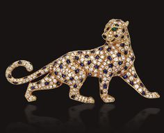 DIAMOND AND SAPPHIRE PANTHER BROOCH, CARTIER, PARIS.  The stalking three-dimensional figure decorated with buff-top calibré-cut sapphire spots against a ground of round diamonds, the eyes of pear-shaped emeralds, the nose of carved onyx, mounted in 18 karat gold, signed Cartier, numbered 636529, maker's mark, assay marks.