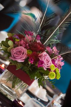 Short flower arrangements with peacock feathers