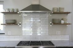 Love the open shelves w/ the range hood.. May go this route.   Stainless range hood with subway tile and shelves instead of cabinets