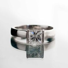 Engagement ring with a princess cut moissanite, set in a half bezel setting that mimics the appearance of a tension set gem stone. The solitaire